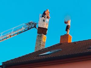 FOTO, VIDEO: Vyjednavači sedm hodin přesvědčovali muže, aby slezl ze střechy domu v Malešicích